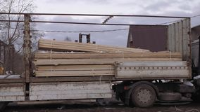 Forklift uploads heavy truck with wood block stacks at sawmill. On cold winter day at dirty road stock footage