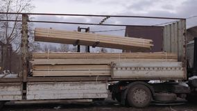 Forklift uploads heavy truck with wood block stacks at woodwork facility. On cold winter day at dirty road stock video footage