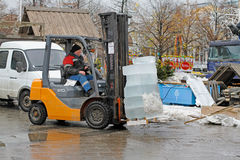A forklift worker makes transportation of ice blocks to storage sites Royalty Free Stock Photos