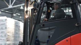 Forklift z Gipsowymi torba stosu przejażdżkami Za kamerą w magazynie zbiory