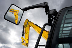 Forklifts. Earth moving machines and forklift arms, one reflected in a side mirror, against a moody sky Royalty Free Stock Images