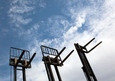 Forklifts. Three forklifts in front of the bright blue sky Royalty Free Stock Photo