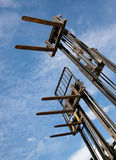 Forklifts. Three forklift machines against a blue sky Royalty Free Stock Photography