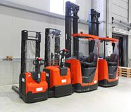 Forklifts. Four red forklift trucks in distribution warehouse Royalty Free Stock Photo