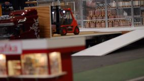 Forklifts loading goods on Truck - Logistics business and shipping facility - miniature car models stock video