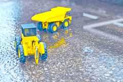 Forklifts and trucks under civil engineering. Toy truck and forklift, water, cement floor Stock Image