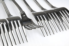 Forks arranged in series on the kitchen table. Royalty Free Stock Photos