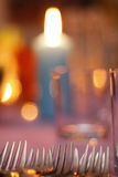 Forks on the dining table. Six forks on the table with the candle in the backgound and glas on the right side Royalty Free Stock Image