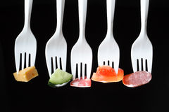 Forks With Food. Five white plastic forks in a row with various food on a black background Royalty Free Stock Photography