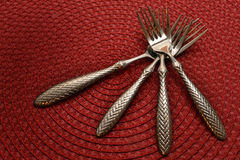 Forks. Four silverware forks crossed on a red placemat background Royalty Free Stock Photo