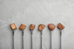 Forks with fried meat fondue pieces on grey, top view. Space for text. Forks with fried meat fondue pieces on grey background, top view. Space for text stock image