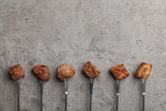 Forks with fried meat fondue pieces on grey, top view. Space for text. Forks with fried meat fondue pieces on grey background, top view. Space for text stock photos