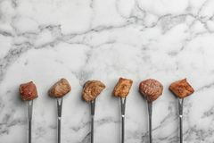 Forks with fried meat fondue pieces on marble background, top view. Space for text stock images