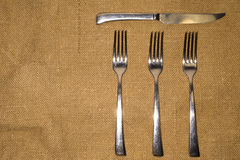 Forks and knife on an old tablecloth Royalty Free Stock Images