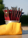 Forks and knifes in a red package, all in a champagne cooler wrapped yellow serviette Royalty Free Stock Photo