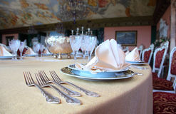 Forks and plates with placemat at dinner table. Four forks and two plates with placemat at the brink of dinner table in restaurant Stock Images