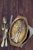Forks, spoons and dish on dark brown background Stock Photo