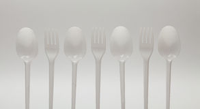 Forks and spoons isolated on white background. Forks and spoons in a row alternately on a white background Stock Images