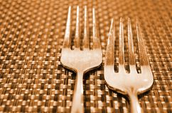 Forks on a straw table. Two forks on a straw place mat Stock Images