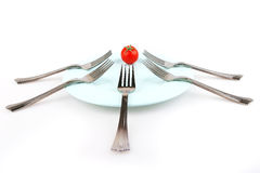 Forks and tomat on dish Royalty Free Stock Photography