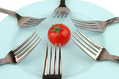 Forks and tomat on dish Stock Image