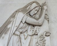 Statue of a desolate woman. Forli, Italy - February 15th 2018: More than 100 hundred sculputure of a desolated woman, placed in the monumental cemetery Royalty Free Stock Photos