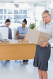 Forlorn businesswoman leaving office after being let go Stock Images