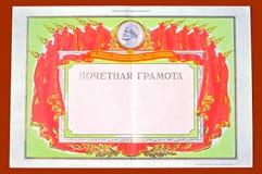 Form av det sovjetiska utmärkelsediplomet på en röd bakgrund Royaltyfri Fotografi