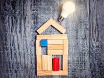Form av huset ovanför träd på mörk träbakgrund och LEDD kula Efterföljd av uppvärmningkoppar eller kokkärl och luftkonditionering Royaltyfri Bild