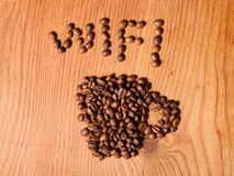 Form a coffee cup made of coffee beans. On the wood background and wi-fi text Stock Image