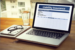 Form Document Liability Insurance Money RIsk. Computing Computer Laptop with screen on table Silhouette and filter sun royalty free stock images