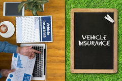Form Document Vehicle Insurance Claim. Businessman working at office desk and using computer and objects, coffee, top view,and ues chalk board Stock Images