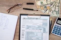 Form, dollar och räknemaskin för skatt 1040 Fotografering för Bildbyråer