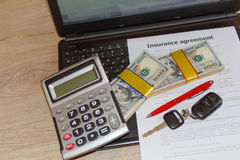 Form för bilförsäkring med biltangenter, penna, mycket dollar, bärbar dator och Royaltyfria Foton