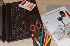 Form för bilförsäkring med biltangenter, penna, mycket dollar, bärbar dator och Arkivbilder