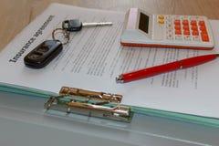 Form för bilförsäkring med den biltangenter, pennan och räknemaskinen på tablen Royaltyfri Foto