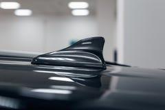 Form för fena för haj för närbildGPS antenn på ett tak av bilen för radio arkivfoto