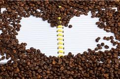 form för hjärta för kaffebönor på anteckningsboken Arkivfoto