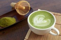 Form för hjärta för Matcha lattekonst överst på trätabellen med någon gr arkivbild