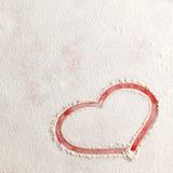 Form för hjärta för valentinförälskelse röd i snö på röd bakgrund royaltyfria bilder