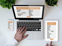 form för personlig information om kontorstabletop online- arkivfoto