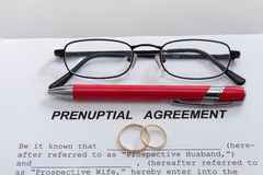 Form för Prenuptial överenskommelse och två vigselringar Royaltyfria Foton