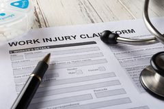 Form för reklamation för skada för arbete för sidosikt med stetoskopet och asken av medicinska piller & försäkringbegreppet arkivfoto