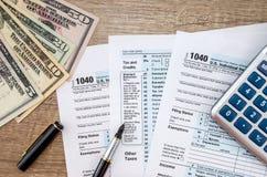 Form för skatt 1040, dollarräknemaskin Fotografering för Bildbyråer
