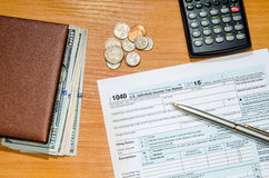 Form för skatt 1040 för 2016 med pennan, exponeringsglas, dollar Arkivbilder