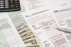 form för skatt 1040 med pennan, dollar, räknemaskin Arkivfoton