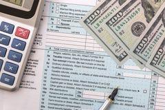 Form för skatt 1040 med räknemaskinen, pennan, exponeringsglas och dollaren Fotografering för Bildbyråer