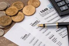 form för skatt 1040, oss mynt, penna Arkivbild