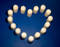 The form of heart from candles. Candles in the form of heart on dark blue stock images