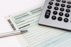 Form of income tax return with pen and calculator. Form of income tax return with ball pen and pocket calculator Stock Photos